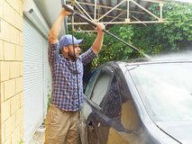 Man washing his black car near house. Royalty Free Stock Photography