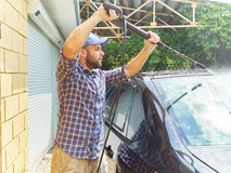 Man washing his black car near house. Stock Photos