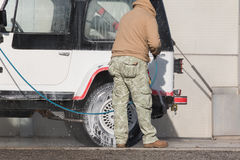 Man washing his car with a jet of water Royalty Free Stock Photo