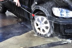Man washing his car under high pressure water in service Stock Photo
