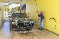 A man washing his car in car-wash bay stock image