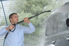 Man washing car with water hose. Man washing his car with water hose Royalty Free Stock Photos