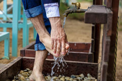 Man washing his feet on the sand beach. Place for washing the feet is made of wooden planks. The flooring is strewn with pebbles. Summer vacation at the Stock Image