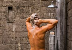 Man washing hair in outdoor shower royalty free stock photos