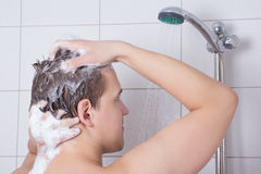 Man washing his hair in shower Stock Photos