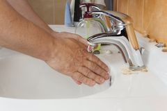 Man washing his hands in the sink. Hygiene Stock Photos