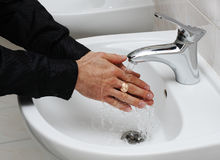 Man washing his hands under running water Royalty Free Stock Photos
