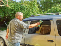 Man washing his silver car near house. Royalty Free Stock Photo