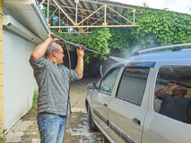 Man washing his silver car near house. Royalty Free Stock Images