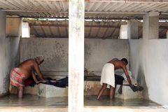 Man washing laundry at Fort Cochin on India Stock Images