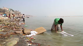 Man washing laundry on shore of Ganges, with city in the background. VARANASI, INDIA - 20 FEBRUARY 2015: Man washing laundry on shore of Ganges, with city in stock video footage