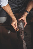 Man washing leather brogues with a sponge Stock Image