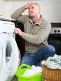 Man and washing machine Stock Images
