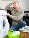 Man and washing machine Stock Images