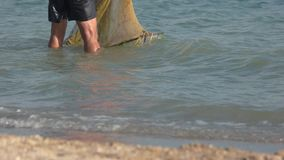 Man is washing the net in the sea. stock footage