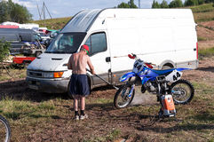 Man washing a race bike after the competition in motocross Royalty Free Stock Photos