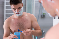 Man washing a razor in the cup with water Royalty Free Stock Image