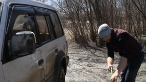 A man washing an SUV with a MOP and a rag from the bucket on the river.  stock video footage