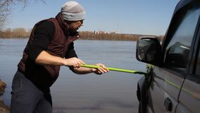 A man washing an SUV with a MOP and a rag from the bucket on the river.  stock footage