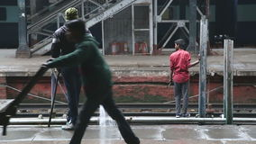 Man washing the train platform while young man stands on railway behind. stock video