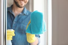 Man washing window glass at home. Man in casual clothes washing window glass at home Stock Photo
