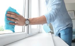Man washing window glass at home. Man in casual clothes washing window glass at home Royalty Free Stock Photos