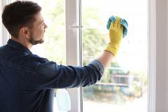 Man washing window glass at home. Man in casual clothes washing window glass at home Royalty Free Stock Photography