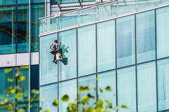 Man washing windows on a glass skyscraper Stock Photo