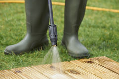 Man Washing Wooden Decking With Pressure Washer Stock Images