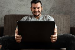 A man watches an adult video on a laptop while sitting on the couch. The concept of porn, men`s needs, pervert, lust, desire, stock images