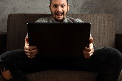 A man watches an adult video on a laptop while sitting on the couch. The concept of porn, men`s needs, pervert, lust, desire, stock image