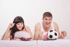Man watches football fanatic wife goes crazy already. Young girl and a guy in bed. Beautiful girl has a manicure, men watches football on TV Royalty Free Stock Photography
