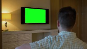 Man Watches Green Screen TV in Luxury Hotel Room. 8431 A man watches a television in a luxury hotel room.  From behind, with green screen for customizable stock video footage