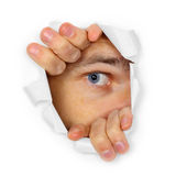 Man watches through a hole Royalty Free Stock Image
