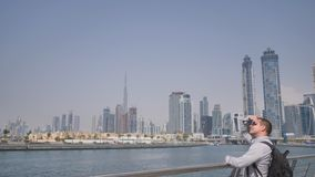 A man watches a panorama of the city with skyscrapers from the Dubai Greek district. A man watches a panorama of the city with skyscrapers from the Dubai Greek stock footage