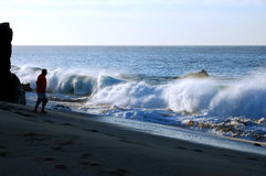 Man Watches Pounding Surf. Man on beach watching pounding surf.  It is early morning. The man is in silohuette and the surf is side lit Royalty Free Stock Image