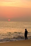Man watches red sun at sunset Stock Images