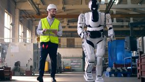Man watches a robot walk in a factory room.