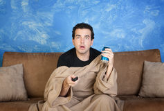 Man Watches Television. Amazed Caucasian man in bathrobe on sofa with can and remote control Royalty Free Stock Photo