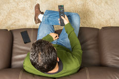 Man watches television. Overhead view, brown couch. royalty free stock photo