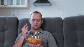 A man watches TV and eats chips stock video footage
