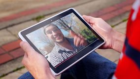 Man watches a viral video vlogger outside on tablet pc. A man outside his home watches a popular vlogger playing on his tablet PC stock footage