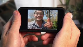 Man watches a viral video vlogger on smartphone. A man watches a popular vlogger video playing on his smartphone stock video footage