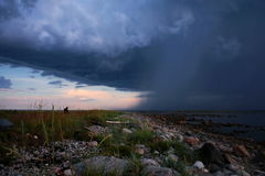 Man watching the approaching storm. Storm clouds coming in from the sea to the shore Stock Photography