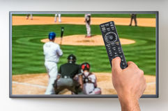 Man is watching baseball match on TV. And holding tv remote controller in hand Royalty Free Stock Photo