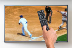 Man is watching baseball match on TV. And holding tv remote controller in hand Stock Photography