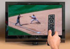 Man is watching baseball match on TV. And holds remote controller in hand Royalty Free Stock Photo