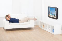 Man watching beach view on tv at home Royalty Free Stock Photos