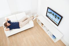 Man watching beach view on tv at home Stock Images