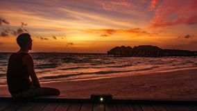 Man watching Beautiful Sunset over the Indian ocean on Maldives Resort Island. stock photography